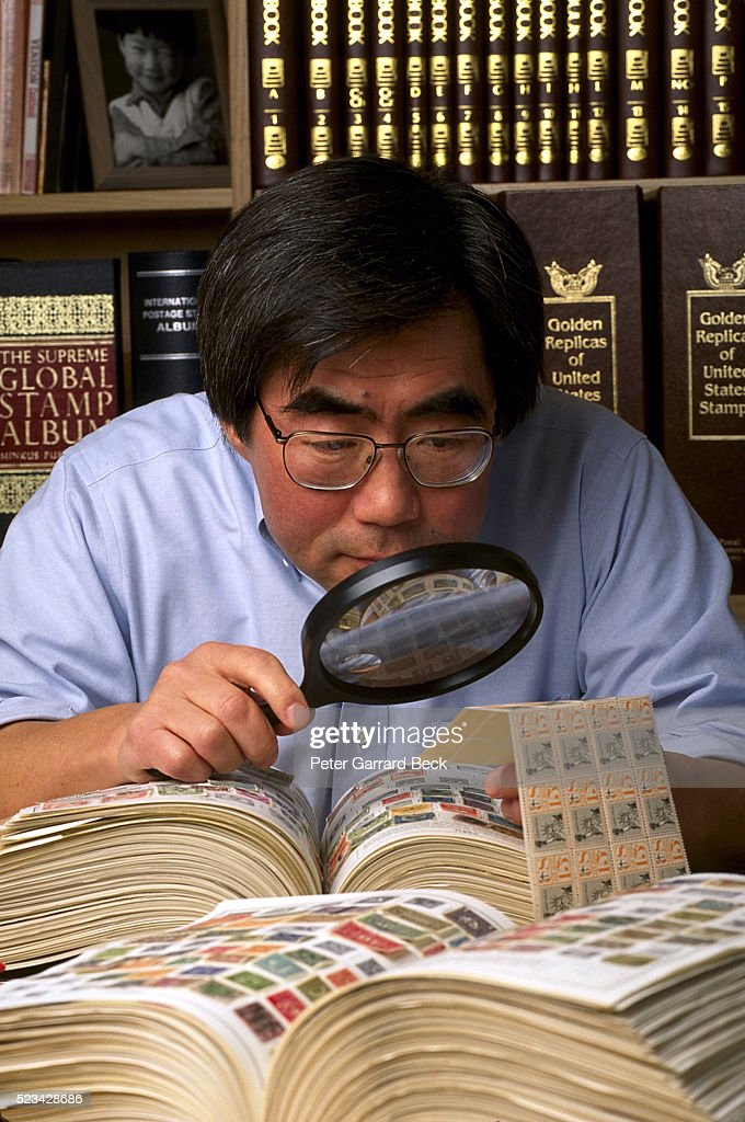 Stamp collector examining stamps : Stock Photo