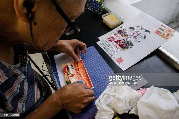 Stamp collector Lok Kachung attaches a stamp issued to mark 20 years since the city was handed back to China by Britain with a design that pays...