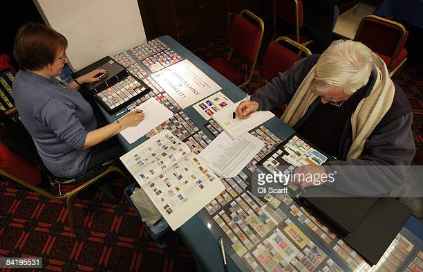 Stamp collectors look through books of stamps for sale at the Strand Stamp Show in the Royal National Hotel on January 7 2008 in London England The...