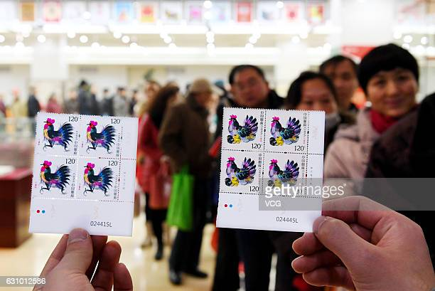 Stamp collectors stand in long lines to buy new set of roosterthemed stamps at a post office building on January 5 2017 in Zhengzhou Henan Province...