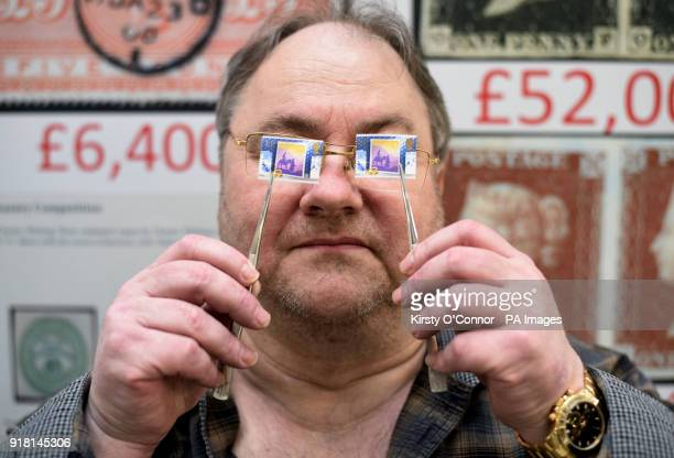 Stamp dealer Mark Bloxham holds up an SG1414a 1988 13p Christmas stamp worth pound8 next to a 14p version worth 14p during the Stampex philatelic...