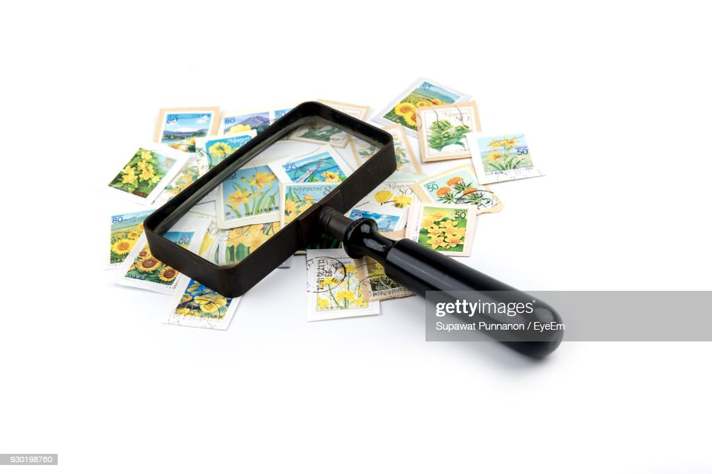 Stamps Collection With Magnifying Glass Over White Background : Stock Photo