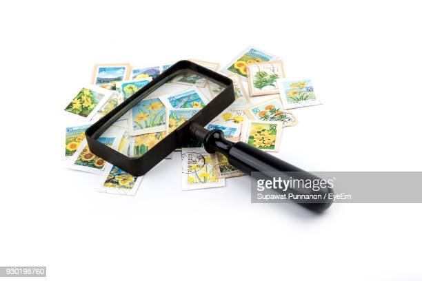 Stamps Collection With Magnifying Glass Over White Background