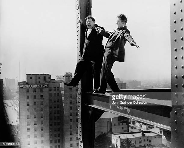 Stan and Ollie balance on a beam at a high rise construction site during a scene from the 1929 comedy Liberty