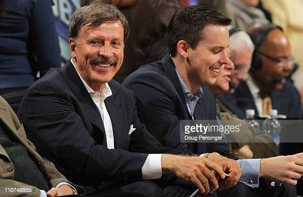 Stan Kroenke along with his son Josh Kroenke watch from courtside seats as the Denver Nuggets host the San Antonio Spurs at the Pepsi Center on March...