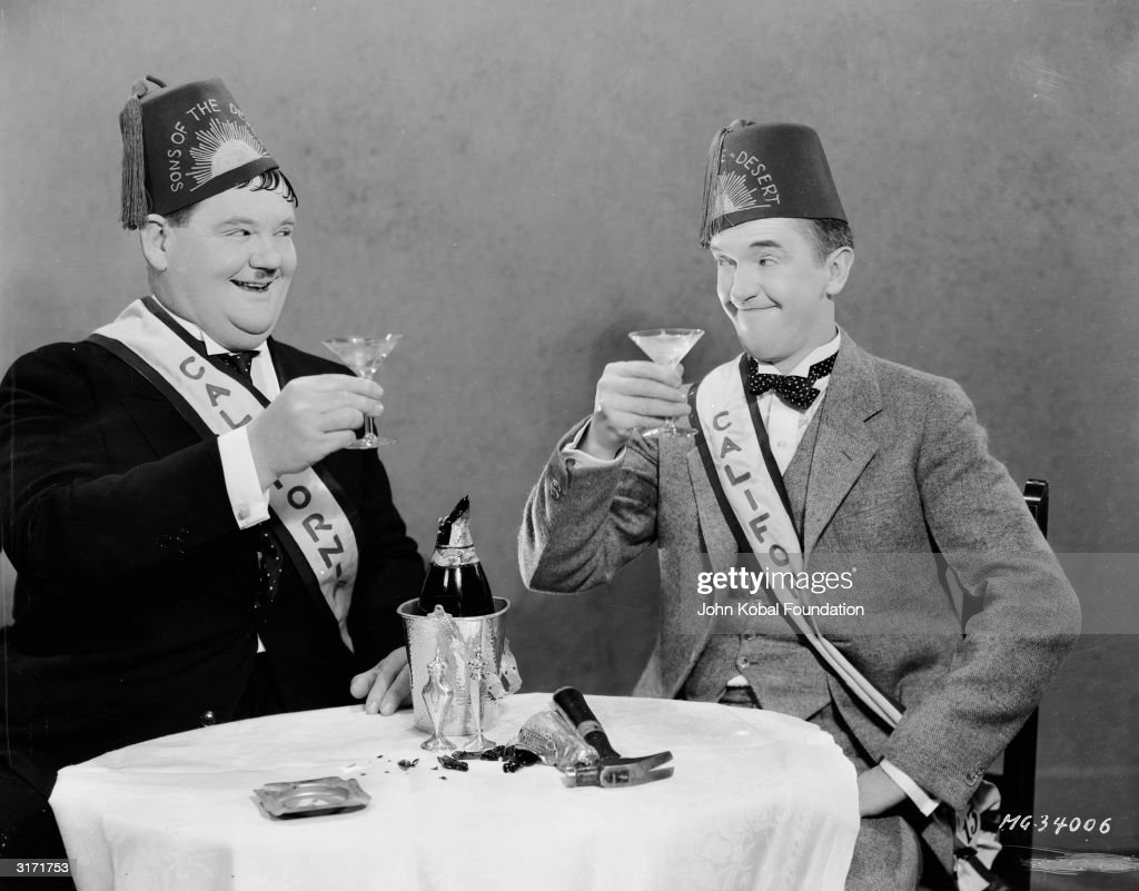 Stan Laurel (1890 - 1965) and Oliver Hardy (1892 - 1957) drink a toast after opening their bottle of champagne with a hammer, in a publicity still for 'Sons Of The Desert', directed by Lloyd French and William A Seiter.