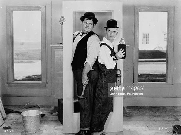 Stan Laurel and Oliver Hardy making things difficult for themselves in a scene from 'The Finishing Touch' directed by Leo McCarey and Clyde Bruckman