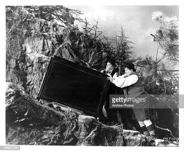 Stan Laurel and Oliver Hardy pushing heavy item up mountain in a scene from the film 'Swiss Miss' 1938