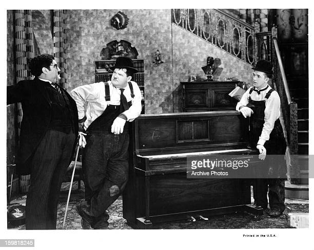 Stan Laurel and Oliver Hardy with a piano in between them in a scene from the film 'The Music Box' 1932