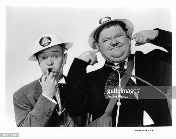 Stan Laurel blows a whistle next to Oliver Hardy in publicity portrait for the film 'Air Raid Wardens' 1943