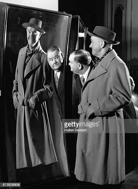 Stan Laurel inspects his reflection in a distorting mirror at Madame Tussaud's 1947