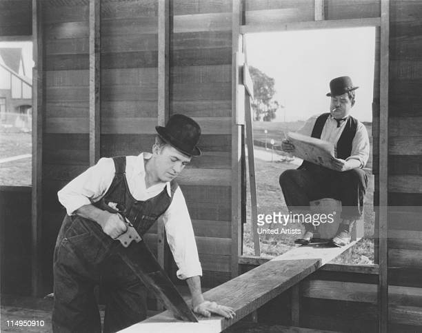 Stan Laurel saws a plank on which Oliver Hardy is sitting in a scene from 'The Finishing Touch' directed by Leo McCarey and Clyde Bruckman 1928