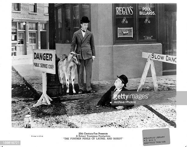 Stan Laurel standing on the sidewalk with a goat while Oliver Hardy stands in waist deep mud looking up at him in a scene from the documentary 'The...