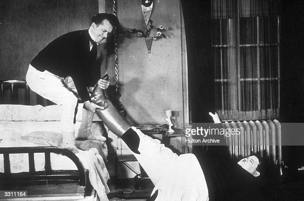 Stan Laurel tries to pull the boots off Oliver Hardy in a scene from the film 'Be Big' directed by James Parrott for Hal Roach/ MGM
