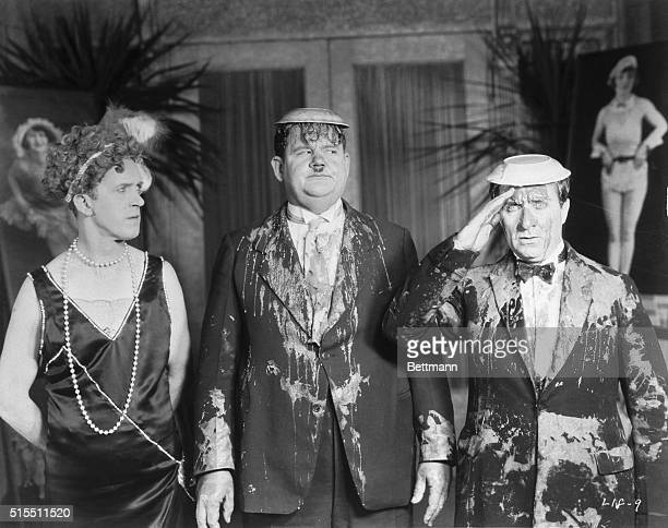 Stan Laurel wearing a dress looks at Oliver Hardy and another actor covered with pie in a movie still