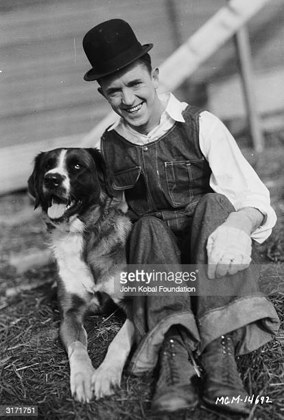 Stan Laurel with a dog during a break from filming 'The Finishing Touch' directed by Leo McCarey and Clyde Bruckman