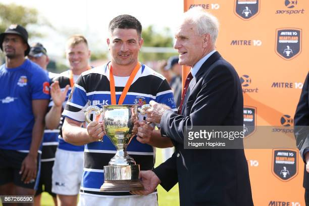 Stan Meads brother of Colin Meads hands the Colin Meads Cup to captain Cole Baldwin of Wanganui during the Meads Cup Final match between Horowhenua...