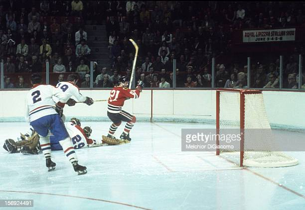 Stan Mikita of the Chicago Blackhawks skates on the ice as Terry Harper goalie Ken Dryden and Jacques Laperriere of the Montreal Canadiens defend...