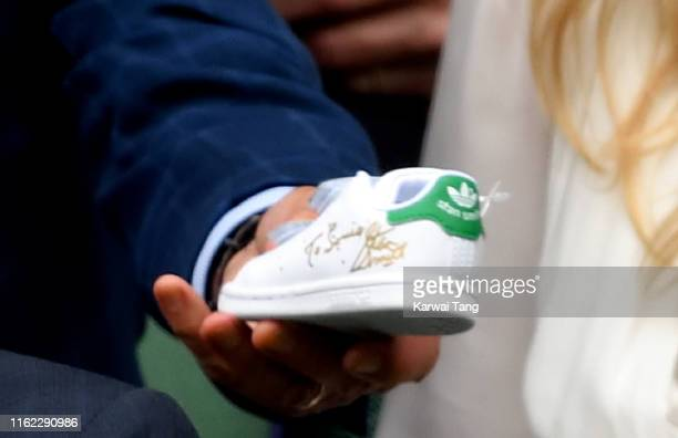 Stan Smith gives Catherine Duchess of Cambridge a signed baby 'Stan Smith' trainer in the Royal Box during Men's Finals Day of the Wimbledon Tennis...