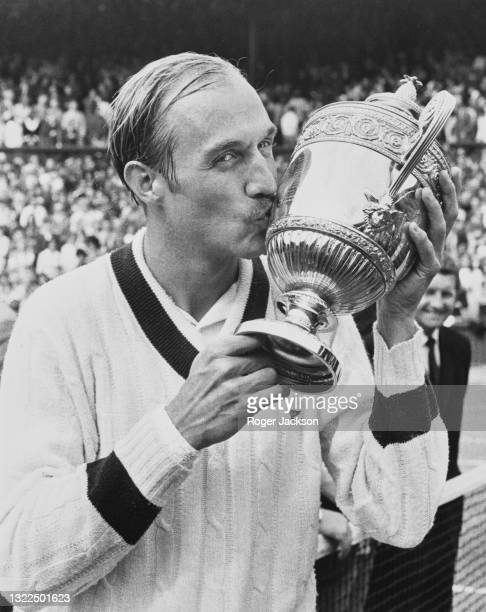 Stan Smith of the United States poses for photographs and kisses the Gentlemen's Singles Trophy following his victory over Ilie Nastase of Romania in...