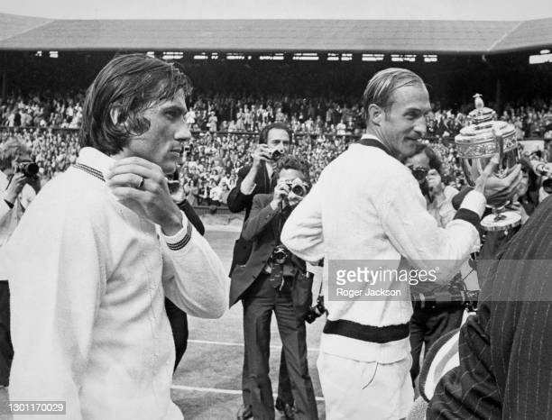 Stan Smith of the United States poses for photographs holding the Gentlemen's Singles Trophy beside the defeated Ilie Nastase following their Men's...