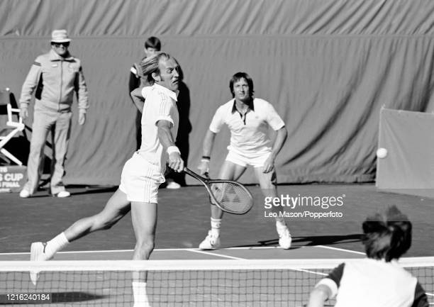 Stan Smith of the United States returns the ball as doubles partner Bob Lutz looks on during the 3rd rubber against David Lloyd of Great Britain and...