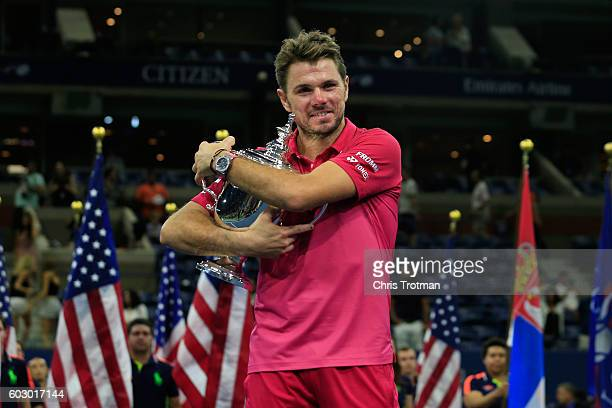 Stan Wawrinka of Switzerland celebrates with the trophy after winning 6-7, 6-4, 7-5, 6-3 against Novak Djokovic of Serbia during their Men's Singles...