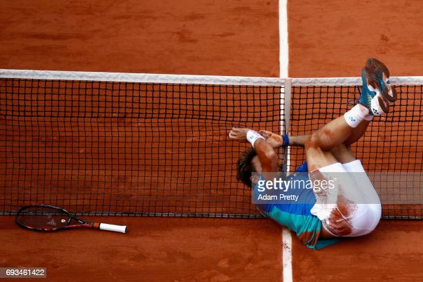 Stan Wawrinka of Switzerland falls into the net after playing a shot during mens singles quarter finals match against Marin Cilic of Croatia on day...
