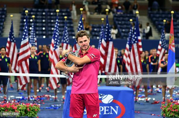 TOPSHOT Stan Wawrinka of Switzerland poses with the championship trophy after defeating Novak Djokovic of Serbia in their 2016 US Open Men's Singles...