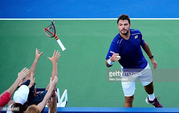 Stan Wawrinka of Switzerland throws his broken racket to fans during his Men's Singles Third Round match against Ruben Bemelmans of Belgium on Day...