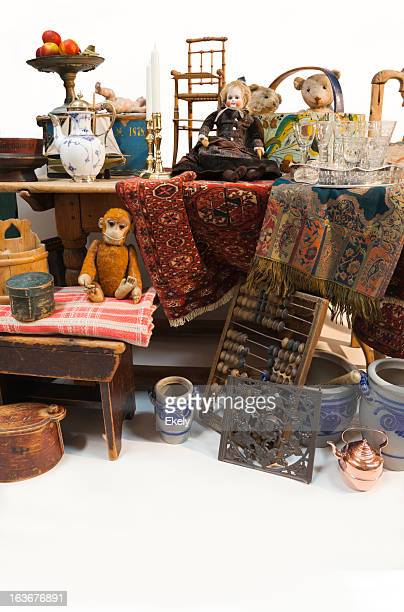 Stand at an outdoor market with antique wooden furniture.