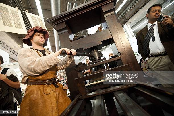 A stand attendant in traditional garb demonstrates the use of a Gutenberg printing press at the 63rd Frankfurt Book Fair October 14 2011 This year's...