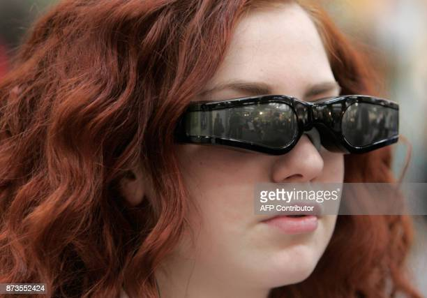 A stand employee demonstrates the use of German manufactuter Carl Zeiss' Cinemizer video glasses at the CeBIT trade fair in Hanover on March 4 2008...