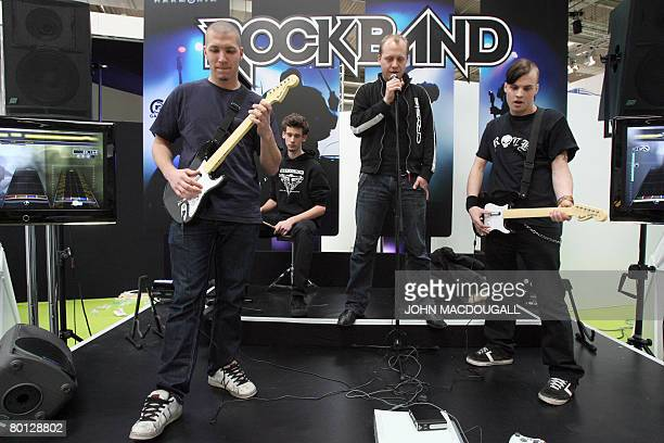 """Stand employees demonstrate the video game """"Rock Band"""" developed by Harmonix Music Sytems at the CeBIT trade fair in Hanover on March 5, 2008. The..."""