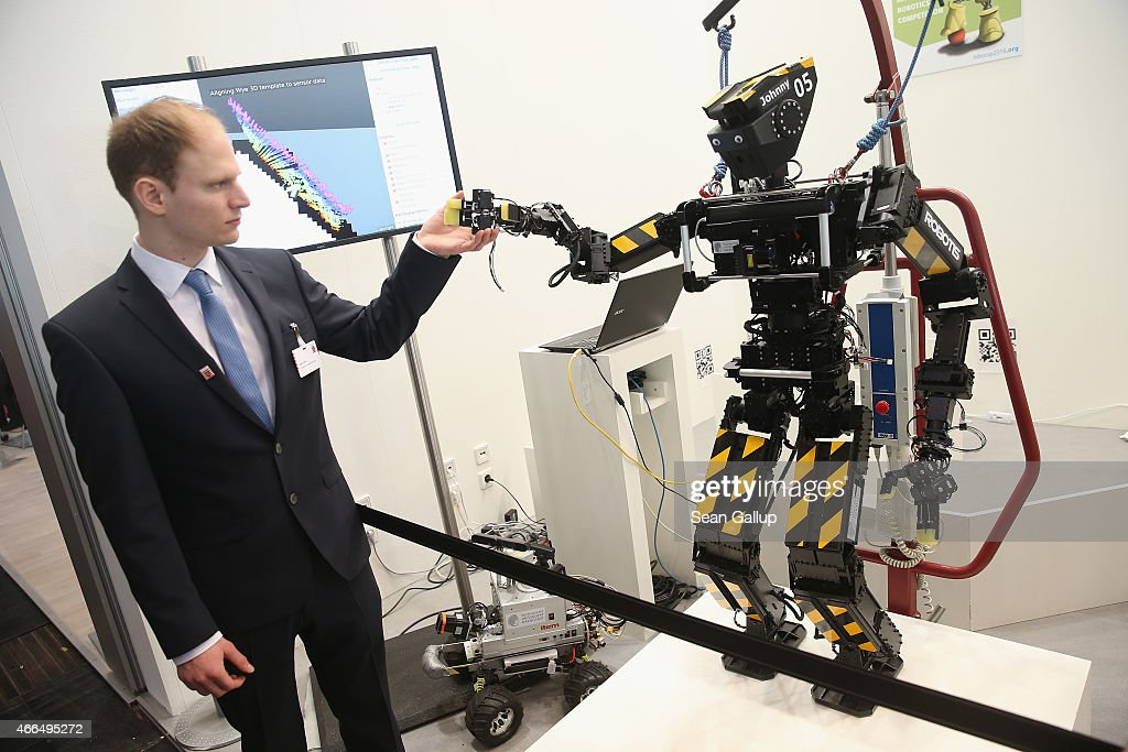 A stand host holds the hand of a robot developed by the University of Darmstadt and intended for hazardous operations at the 2015 CeBIT technology trade fair on March 16, 2015 in Hanover, Germany. China is this year's CeBIT partner. CeBIT is the world's largest tech fair and will be open from March 16 through March 20.
