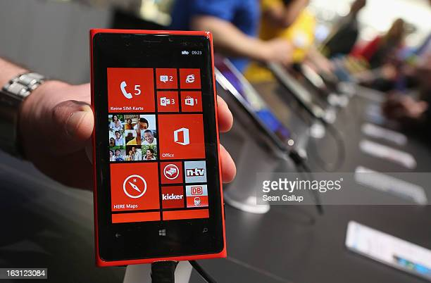 A stand host holds up a Nokia Lumia 920 Windows enabled smartphone at the Microsoft stand at the 2013 CeBIT technology trade fair on March 5 2013 in...
