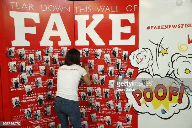 A stand hostess attaches a photo to a wall themed against Fake News at the annual republica conferences on their opening day on May 2 2018 in Berlin...