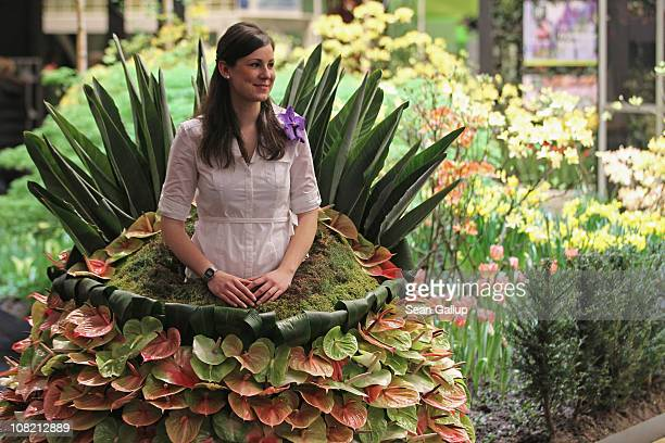 A stand hostess dressed in fresh garden plants stands next to flowers on display at the Netherlands hall at the 2011 Gruene Woche agricultural trade...