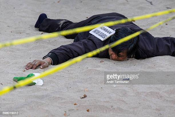 Stand in to the murdered police officer Wayan Sudarsa is seen at the crime scene during the murder reenactment on August 31 in Kuta Bali Indonesia...