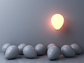 Stand out from the crowd and different concepts One light balloon glowing and floating above other white balloons on white wall background with window reflections and shadows 3D rendering