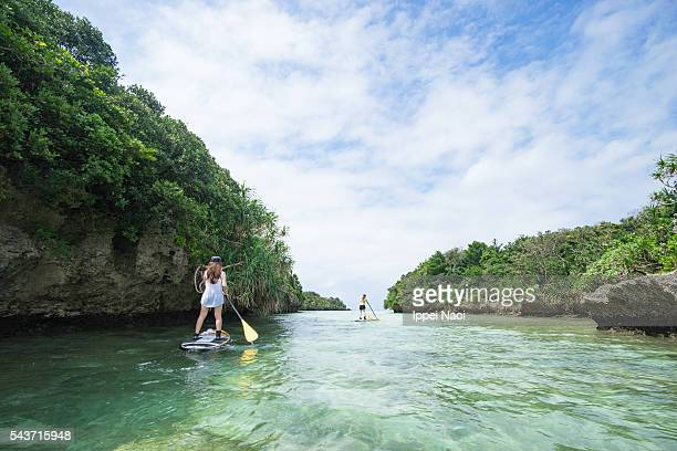 Stand up paddle boarding (SUP) around rock islands in tropical lagoon, Okinawa, Japan