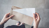 Stand up woman holding white folded a4 paper and brown envelope