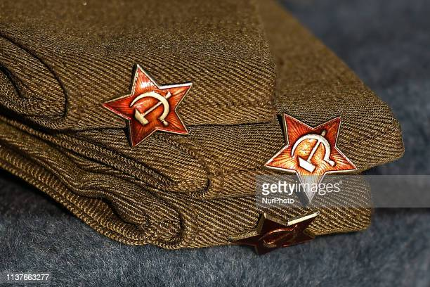 A stand with a Russian WW2 military hat pilotka with Soviet Red Star badge seen on display in a street market located in Kazimierz area of Krakow On...