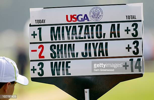 A standard bearer holds a scoreboard during the continuation of round two of the 2010 US Women's Open at Oakmont Country Club on July 10 2010 in...