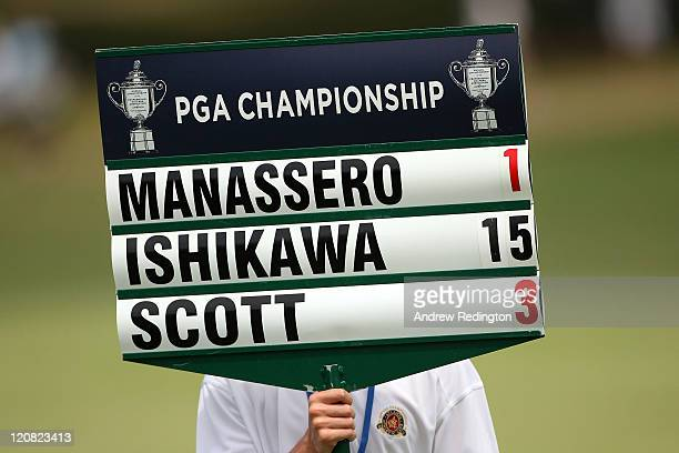A standard bearer shows the scores of Ryo Ishikawa of Japan Matteo Manassero of Italy and Adam Scott of Australia during the first round of the 93rd...