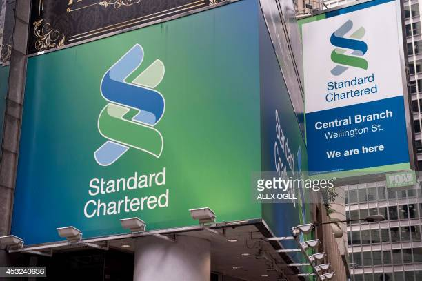 Standard Chartered billboards hang above a bank branch in Hong Kong on August 6 2014 Standard Chartered confirmed that it faces fresh US fines over...