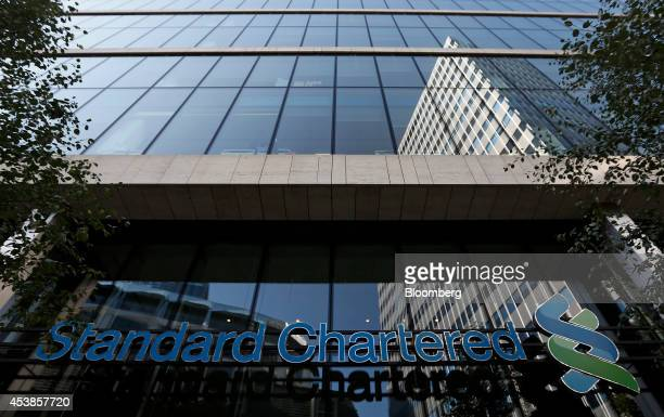 A Standard Chartered Plc logo sits on a wall above the entrance to the company's headquarters in London UK on Wednesday Aug 20 2014 Standard...