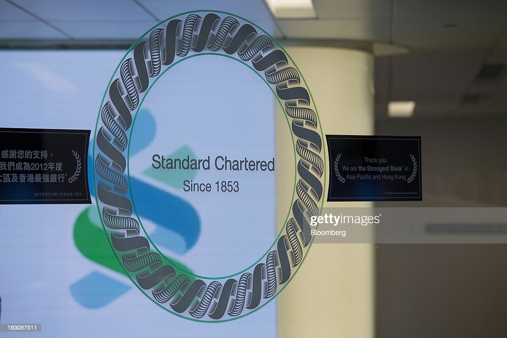 Standard Chartered Plc signage is displayed on the door of one of the banks branches in Hong Kong, China, on Saturday, March 2, 2013. Standard Chartered is scheduled to release annual results on March 5. Photographer: Jerome Favre/Bloomberg via Getty Images