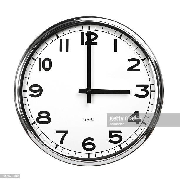 A standard clock displaying three o'clock