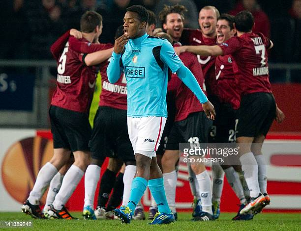 Standard Liege's Congolese striker Michy Batshuayi walks off as Hanover 96 players celebrates at the final whistle of the secondleg of the UEFA...
